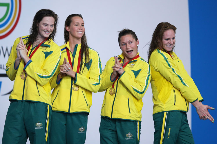 The medley relay team strikes a 'Charlie's Angels' pose on the podium. Photo: Getty