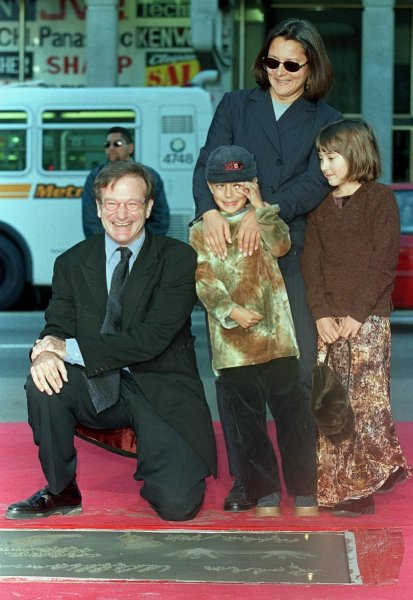Robin Williams poses with son Cody (C), daughter Zelda (R) and ex-wife Marsha with his Hollywood handprint plaque.