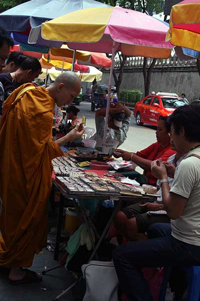 Buddhist-monk-browses-at-Bangkok's-Amulet-Market
