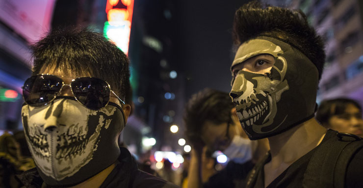 Masked protesters stand at the barriers dividing the police from the crowds in Hong Kong.