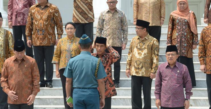 Indonesian President Joko Widodo adjusts his Muslim cap in front of his new cabinet.
