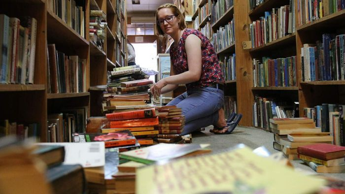 Sam Colwell removes water-damaged books from the shelves at Archives Fine Books in the Brisbane CBD.