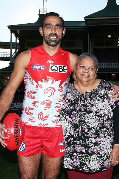 Adam Goodes, his mother Lisa Sansbury and the Indigenous Round guernsey she designed. Photo: Getty