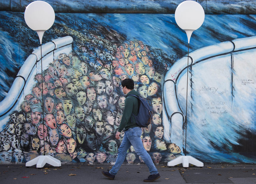 """A man passes by the """"light border"""" installation along remains of the Berlin wall."""