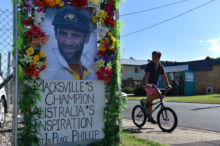 A boy rides his bicycle next to a portrait Hughes in his home town of Macksville. Photo: Getty