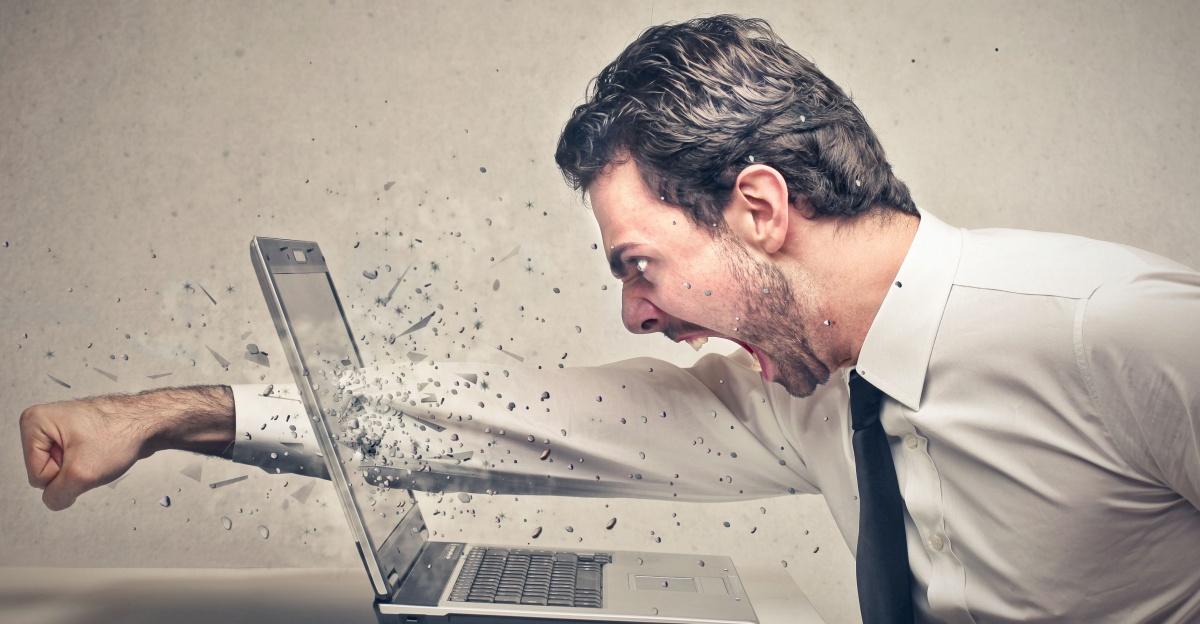 man smashes laptop