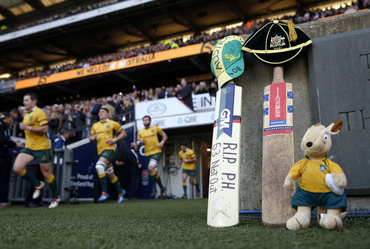 The Wallabies run on to the pitch beside a cricket bat and Australian mascot for the rugby Test against England at Twickenham. Photo: Getty