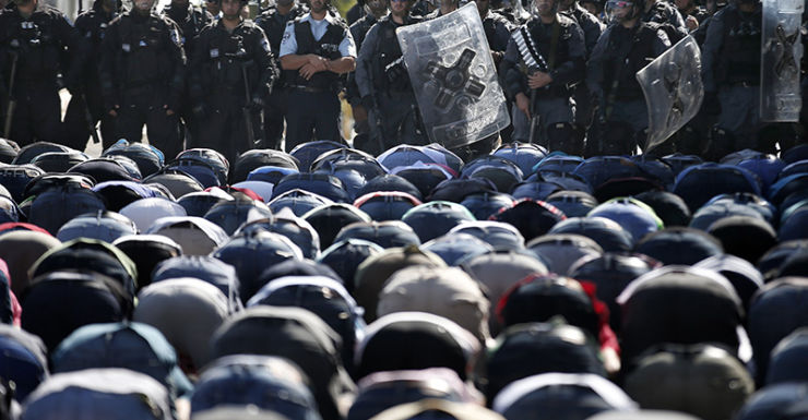 Getty. Israel police and Palestinian people praying.