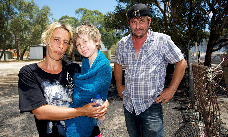 Rachael and Owen Barron next to their home which was saved by firefighters. Photo: AAP