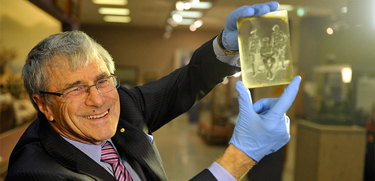 Stokes with holding up a glass negative from WW1 at the Australian War Memorial in Canberra, Thursday, Aug. 9, 2012. It was one of 800 artefacts he donated. Photo: AAP