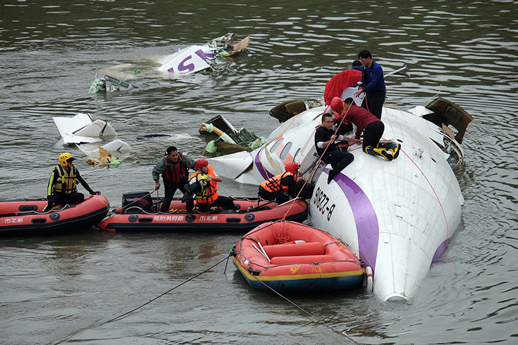 Rescue personnel work to free passengers from a TransAsia ATR 72-600 turboprop plane that crash-landed into a river outside Taiwan's capital Taipei on Wednesday. Photo: Getty