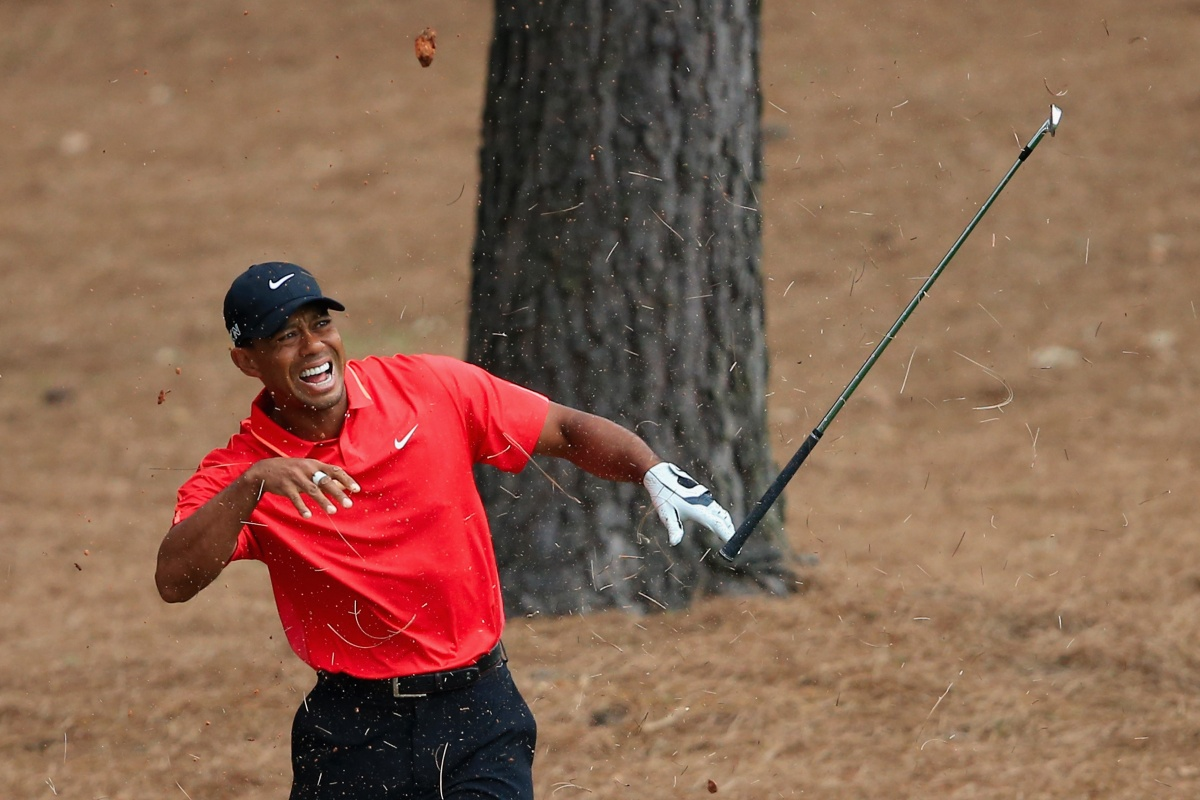 Tiger Woods shows his discomfort after connecting with a tree root in the pine straw on the ninth.