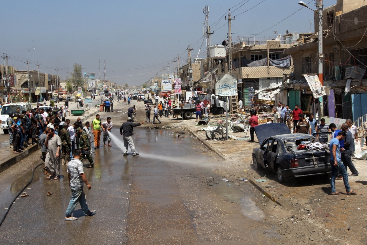 Iraqi bystanders gather at the site of a car bomb in the Al-Amil district.