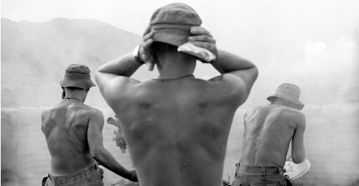 Soldiers cover their ears as they fire a large weapon during the Vietnam War.