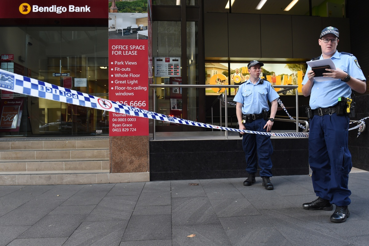 Police officers guard a crime scene following a robbery at a Sydney bank.