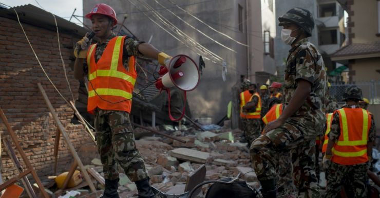 Nepalese Army work to dig up a little boy believed to be in the rubble of a house that collapsed.