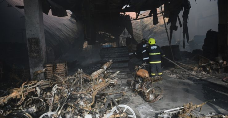 Firemen put out a fire after it gutted a footwear factory in Manila.