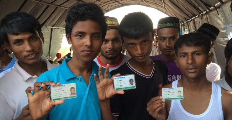 Rohingyas including Muhammad Rafique (r) at Aceh, show their UNHCR refugee cards.