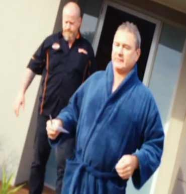 Baron in terry-toweling robe and one of his former colleagues on secret camera footage shown on A Current Affair.