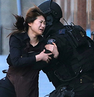 A hostage runs to a police officers for safety escaping from the cafe under siege.
