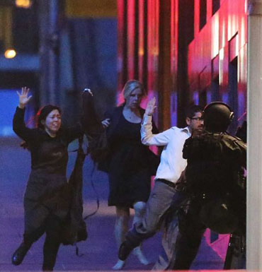 Escaped hostages run with their hands up from the Lindt Cafe during the siege.