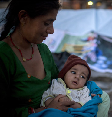 A woman and child sit in the open area in case of an after shock following a second major earthquake