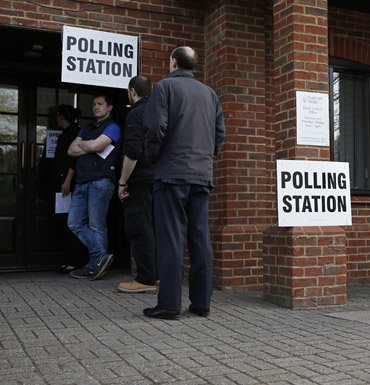 Members of the public wait to cast their votes at a polling station in Elvetham Heath in southern England