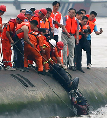 Divers extract a passenger from the river.
