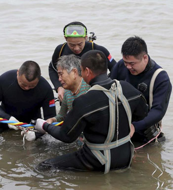A woman is helped after being pulled out by divers from a sunken ship cabin.