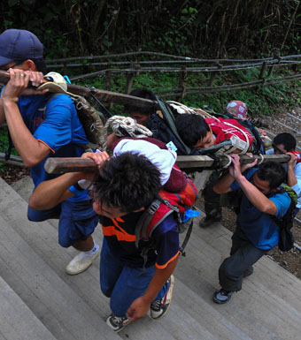 Malaysian rescue team carrying an injured Singaporean student after the quake.