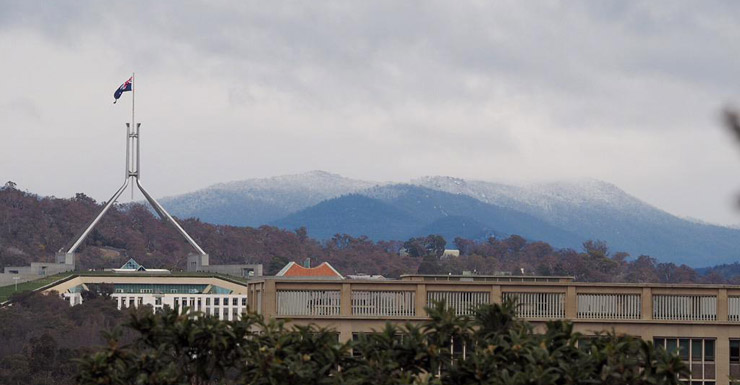 Snow capped mountains in Canberra, with Parliament House in the foreground.