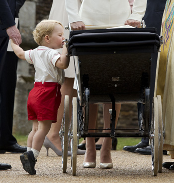 Prince George peeks at sister Princess Charlotte.