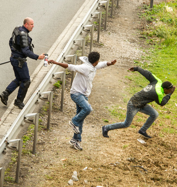 A police officer sprays tear gas onto migrants trying to access the Channel Tunnel in Calais.