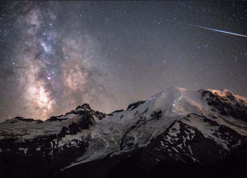 A meteor can be seen piercing through the darkness as the Milky Way towers above the 4,392m peak of Mount Rainier in Washington, USA.