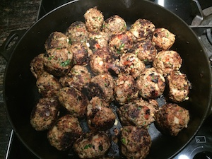 The meatballs sizzle in their pan.