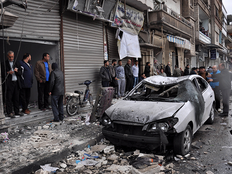 Syrian residents and security forces inspect the damage following a car bomb explosion on April 10, 2015, in the government-controlled majority Alawite neighbourhood of Hay al-Arman, located on the outskirts of the Zahraa district in Homs city. One child was killed and at least 10 people were wounded in the explosion, the Syrian Observatory for Human Rights said. AFP PHOTO / STR (Photo credit should read -/AFP/Getty Images)