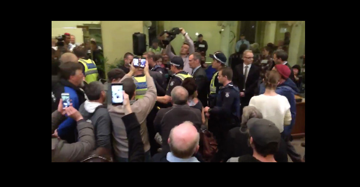 Police escorted the mayor out of the building.