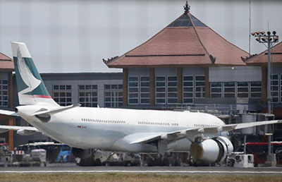 epa04947990 A Cathay Pacific aircraft is parked at Bali's Ngurah Rai International Airport after it made an emergency landing in Bali, Indonesia, 25 September 2015. The Airbus A330 Flight CX170 with 251 passengers on board, which was enroute from Perth, Australia, to Hong Kong, China, landed safely in Denpasar after an engine caught fire mid-flight, the airline later confirmed. EPA/MADE NAGI