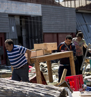 Residents carry furniture between debris caused by the sea in the port of Coquimbo.