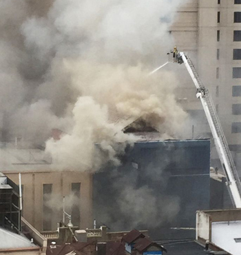 Firefighters tackle the fire from above.
