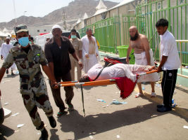 Hajj pilgrims and Saudi emergency personnel carry a woman on a stretcher at the tragedy site. Getty