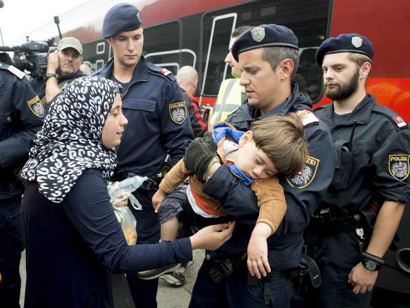 Austrian policemen are helping children and mothers to board a train in the Austrian village of Nickelsdorf.