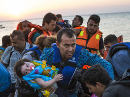 FILE - In this Aug. 13, 2015 file photo, a man carries a girl in his arm as they arrive with other migrants just after dawn on a dinghy after crossing from Turkey to the island of Kos in southeastern Greece. Greece has become the main gateway to Europe for tens of thousands of refugees and economic migrants, mainly Syrians fleeing war, as fighting in Libya has made the alternative route from north Africa to Italy increasingly dangerous. (AP Photo/Alexander Zemlianichenko, File)