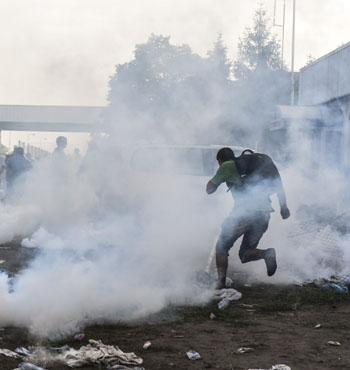 Migrants try to flee from the tear gas.