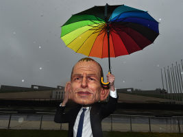 A man wearing a Prime Minister Tony Abbott mask at a Oxfam protest against climate change outside Parliament House in Canberra, Tuesday, June 16, 2015. (AAP Image/Mick Tsikas) NO ARCHIVING