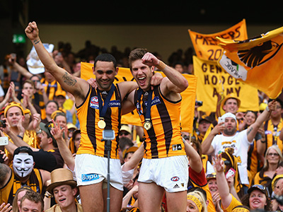 MELBOURNE, AUSTRALIA - OCTOBER 03: Shaun Burgoyne and Grant Birchall of the Hawks celebrate with the crowd after winning the 2015 AFL Grand Final match between the Hawthorn Hawks and the West Coast Eagles at Melbourne Cricket Ground on October 3, 2015 in Melbourne, Australia. (Photo by Quinn Rooney/Getty Images)