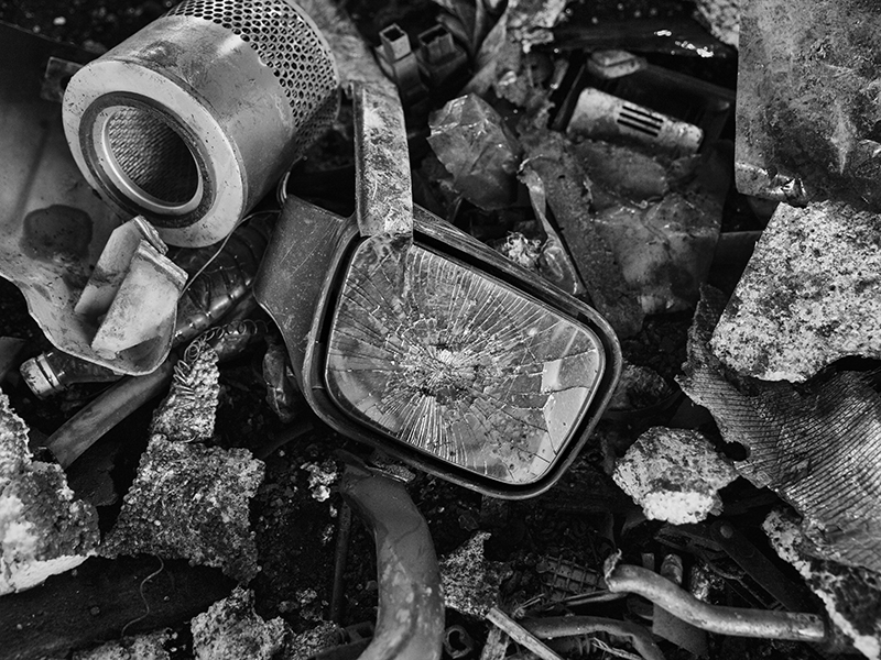 ZHEJIANG, CHINA - SEPTEMBER 25: (EDITORS NOTE: This image has been converted to Black and White) A cracked mirror and other parts from high polluting vehicles taken off the road by authorities are seen at an auto scrapyard on September 25, 2015 in Zhejiang, China. The scrapyard is part of a Chinese government program to remove tens of thousands of polluting vehicles from the nations roads in an effort to curb carbon emissions. In 2014, China announced it would cut carbon emissions in the coming decade as part of global agreements on climate change. (Photo by Kevin Frayer/Getty Images)
