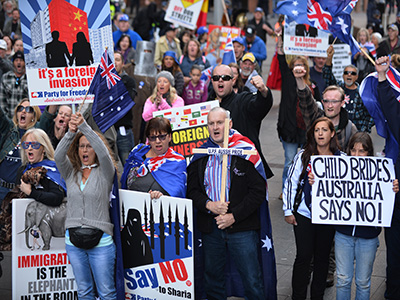 """Nationalist demonstrators protest at a """"Reclaim Australia"""" rally against Islamic extremism in Sydney on July 19, 2015. Reclaim Australia held rallies around the country in which hundreds of people, many waving Australian flags and carrying signs demonstrated against Islamic extremism which also prompted counter anti-racism protests. AFP PHOTO / Peter PARKS (Photo credit should read PETER PARKS/AFP/Getty Images)"""