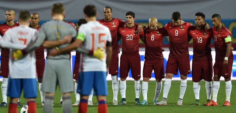 Portuguese and Russian players observe a minute's silence before their friendly. Photo: AAP