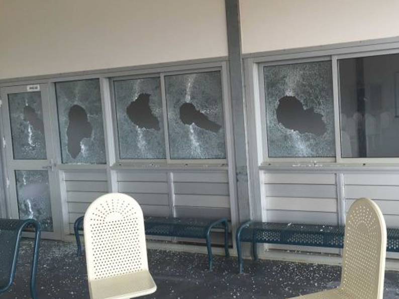 One detainee appears to throw a dangerous weapon, another holds a machete. Photo: Dep. of Immigration.
